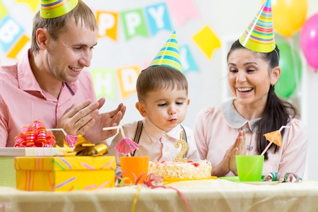 kid boy blowing candle on birthday cake photo