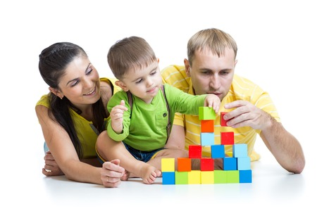 happy family - little boy and parents play building blocks photo