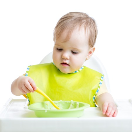 kasha: kid girl eating singly with a spoon Stock Photo