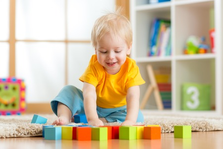 block: kid boy playing  wooden toys at home or kindergarten