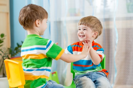 two friends children boys play together indoors Stock Photo