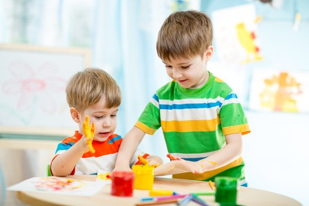 playschool: kids playing and painting at homeor kindergarten or playschool or daycare