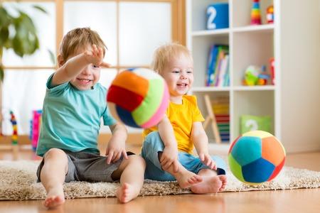 Lächelnde Kinder Jungen spielen mit Ball im Innenbereich Standard-Bild - 35173318