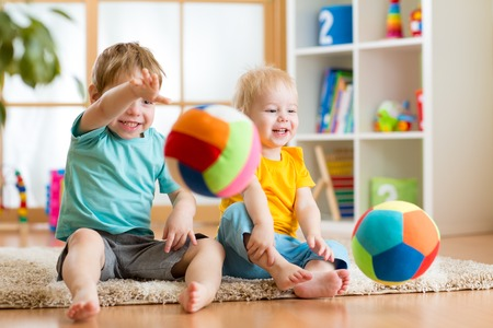 smiling kids boys playing with ball indoors