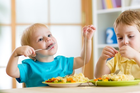 children boys eating healthy food in kindergarten or at home
