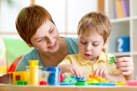 child boy and mother play colorful clay toy at home photo