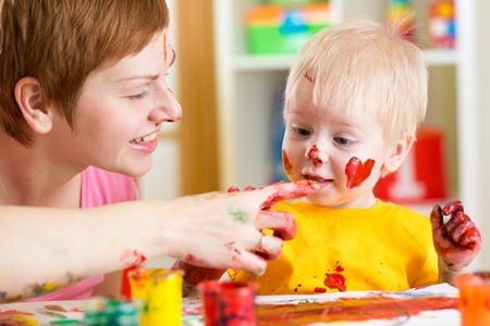manos sucias: madre e hijo niño se divierta con las pinturas en el hogar