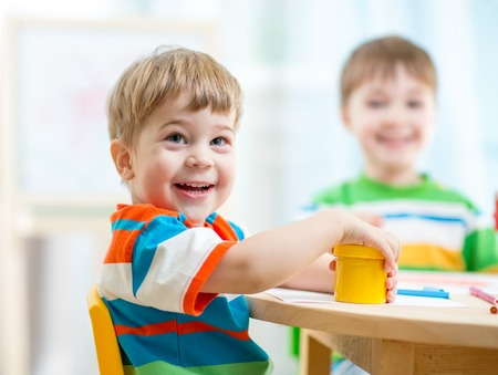day care center: smiling kids painting at home or day care center Stock Photo