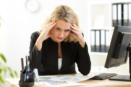 white collar worker: thoughtful businesswoman looking at business papers in office