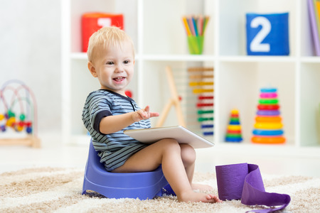 chamber pot: smiling child sitting on chamber pot indoors Stock Photo
