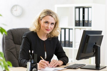 secretary office: Middle-aged pretty business woman working at pc in office