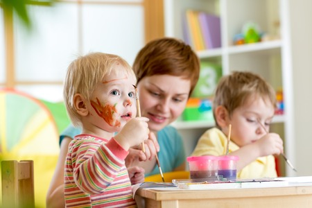 playschool: kids playing and painting at home or kindergarten or playschool