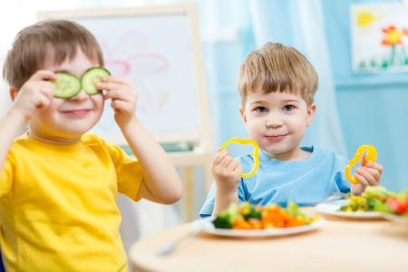 happy kids: kids eating healthy food in kindergarten or at home Stock Photo