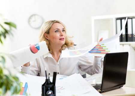 middle-aged businesswoman among huge disorder on table and flying papers photo