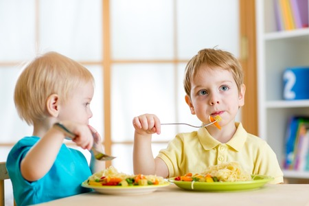 kids preschooler eating food in kindergarten or at home
