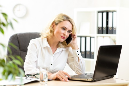 Middle-aged businesswoman working in office. Business lady talking on mobile phone and looking at laptop photo