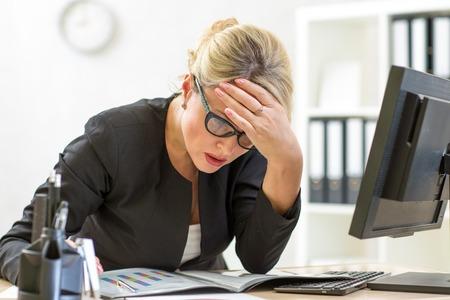 empleados trabajando: reflexivo de mediana edad negocio dama mirando los papeles de negocios en la oficina