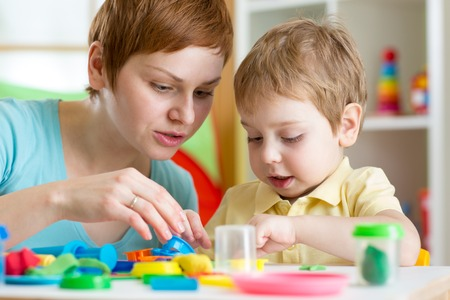 child boy and woman play colorful clay toy at nursery or kindergarten photo