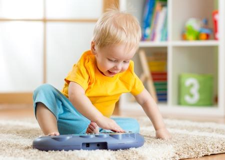 Happy kid toddler boy having fun playing piano toy in nursery photo