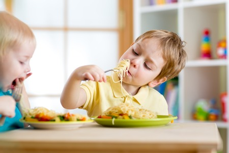 children eating healthy food in nursery or at home