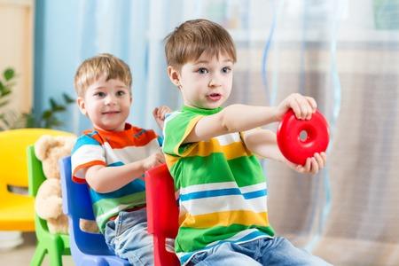 hermanos jugando: Ni�os chicos que viajaban en carros hechos de sillas Foto de archivo
