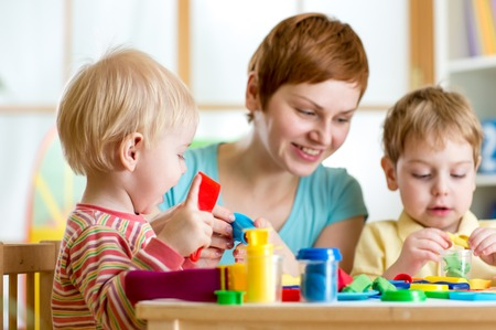 craft materials: mother teaches her children to work with colorful play clay toys Stock Photo