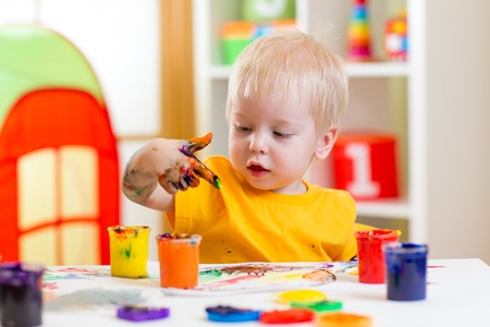 center table: cute kid boy painting at home or playschool