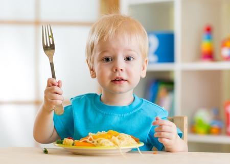 Kind eet gezond voedsel thuis of op de kleuterschool Stockfoto - 35341447