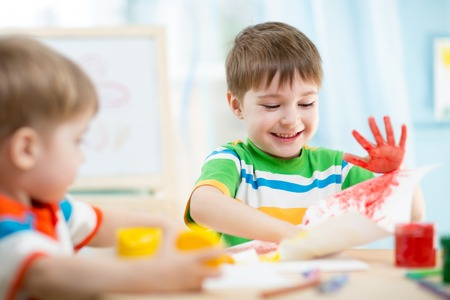 playschool: smiling kids playing and painting at home or kindergarten or playschool