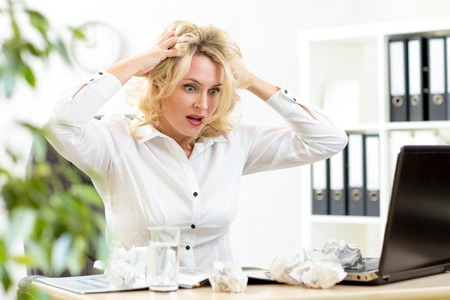 frustration girl: Funny business woman frustrated and stressed holding by head looking at paper heap Stock Photo