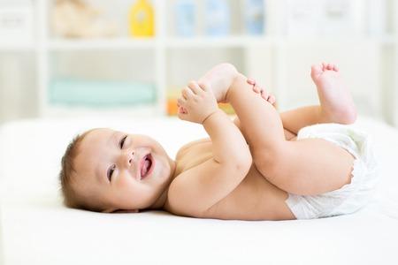 bebes ni�as: beb� acostado en una hoja blanca y la celebraci�n de sus piernas