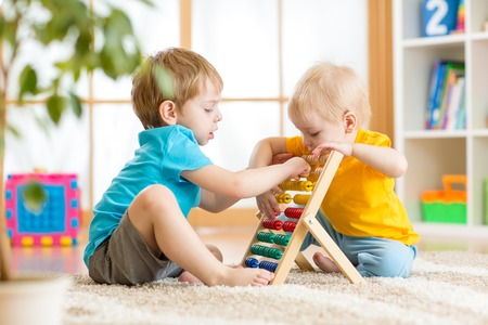 kids boys play with counter toy indoor in nursery or at home photo