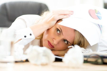 chaos: Businesswoman under pile of documents surrounded crumpled papers Stock Photo