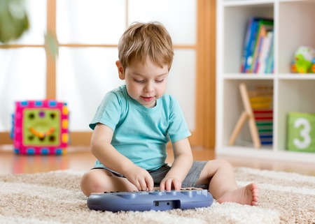 Happy kid boy playing piano toy in nursery photo