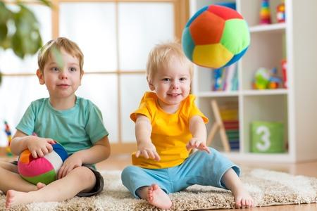 乳幼児: プレイルームでボールで遊ぶ元気な子ども