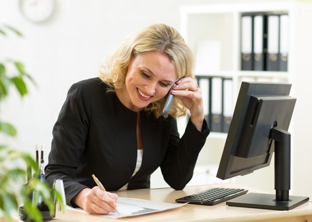 Smiling middle-aged business lady working in office. Woman talking on phone and filling document photo