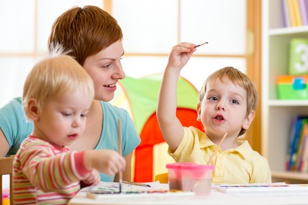 kindergarten: cute mother teaching her kids to paint at home Stock Photo