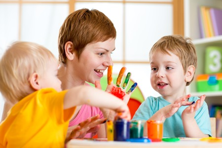 Happy mother and her kids with paint on hands photo