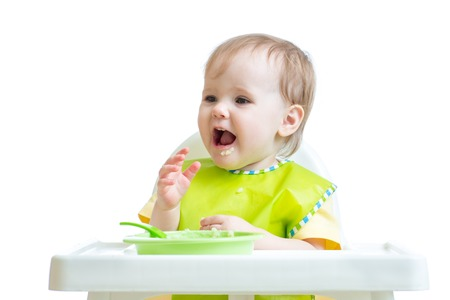 kasha: cheerful happy baby child sitting in chair with a spoon