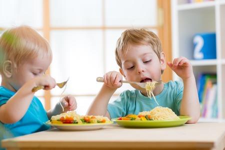 plate of food: bambini che mangiano cibi sani in vivaio o in casa Archivio Fotografico