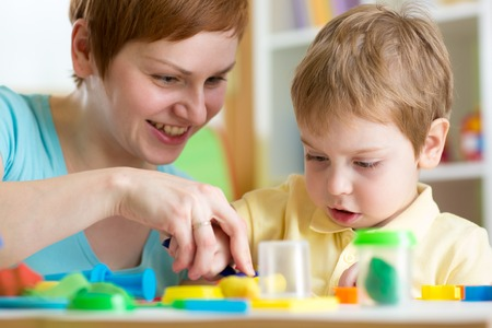 playschool: smiling woman and  child boy play colorful clay toy at playschool or home