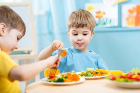 ni�os comiendo: ni�os comiendo verduras en el jard�n de infantes o en casa Foto de archivo