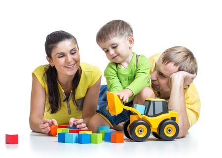children playing with toys: happy family - child boy and parents play building blocks