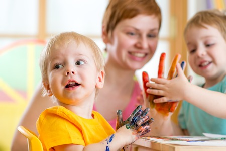 playschool: Cute woman playing and painting with children in playschool or home Stock Photo