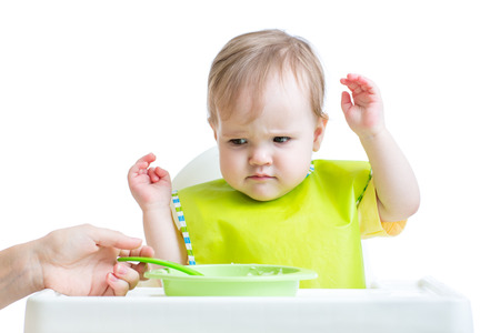 kasha: fretful child sitting in chair refuses to eat Stock Photo