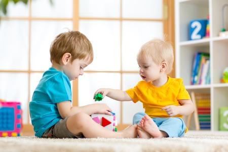dvě děti kluci spolu hrají vzdělávací hračky v herně