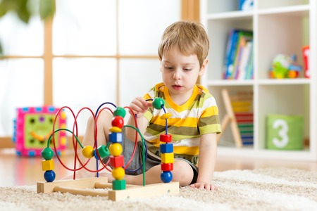 kid boy plays with educational toy indoors photo