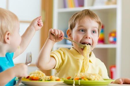 kinderen eten van voedsel in kinderdagverblijf of thuis Stockfoto