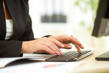 inputting: businesswoman hands typing documents on keyboard of computer