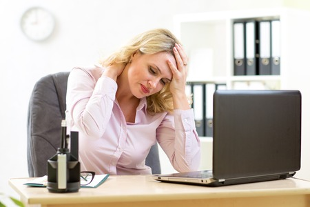 unhappy worker: middle-aged businesswoman with headache having stress in the office